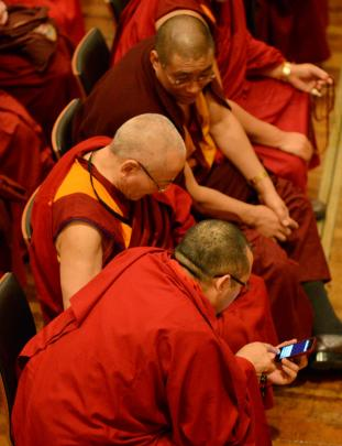 Buddhist monks with their cellephones before the Dalai Lama's speech in the Dunedin Town Hall.