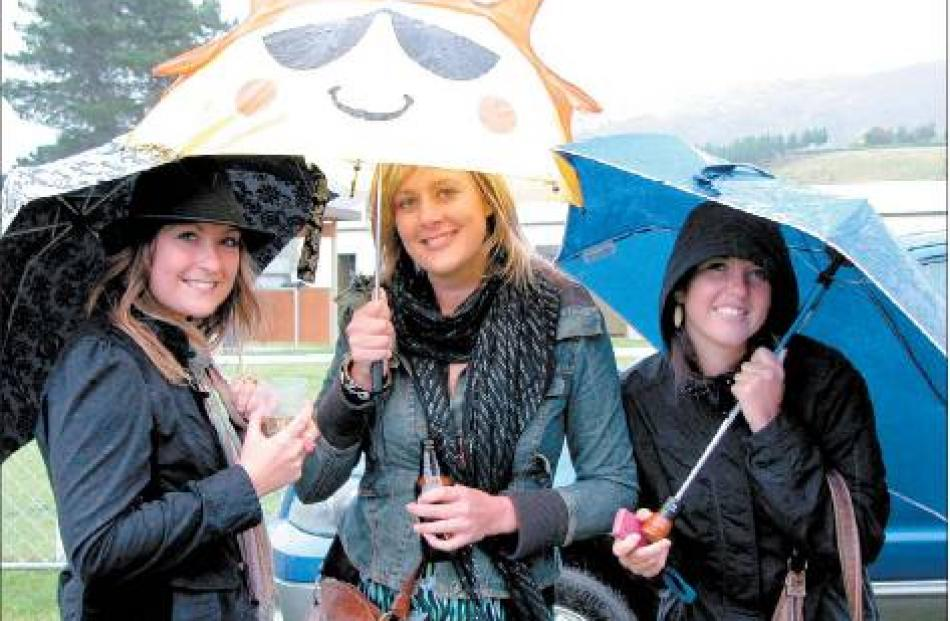 Sunny smiles: The rain did not dampen the good spirits of Queenstown residents (from left) Lucy...