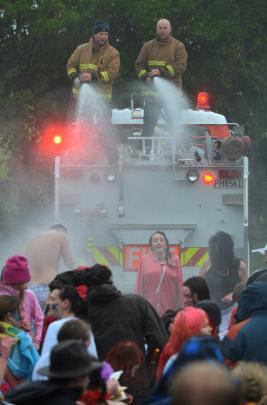 Firefighters Blair Harcus (left) and Robin Hulsbosch spray Polar Plunge swimmers with warm water...