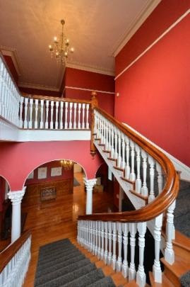 The sweeping staircase was once splattered with paint.