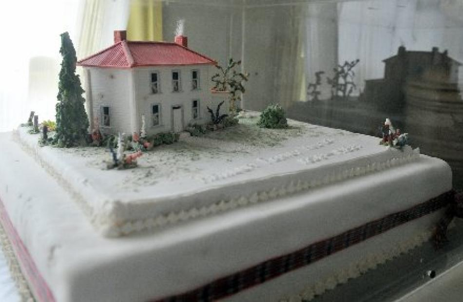 A cake made in 1988 for a local anniversary is preserved under glass.