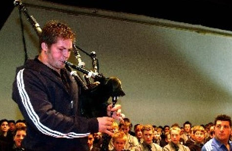 Richie McCaw plays the bagpipes and fellow All Black Byron Kelleher looks on during an assembly...