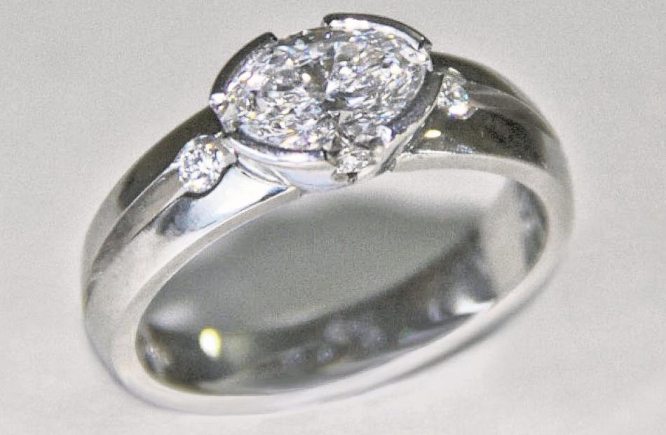 Platinum ring with one large oval and four small diamonds by Tony Williams.