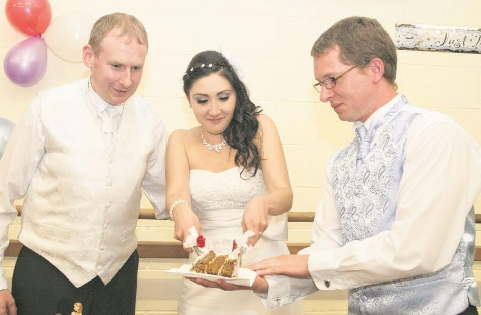 Christopher Swift and Larisa Matiagina try their wedding cake at their reception in April.