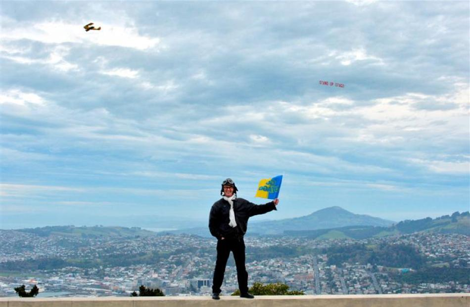 Dunedin North Labour MP David Clark flies his flag  at Signal Hill as a Tiger Moth tows a ''Stand...