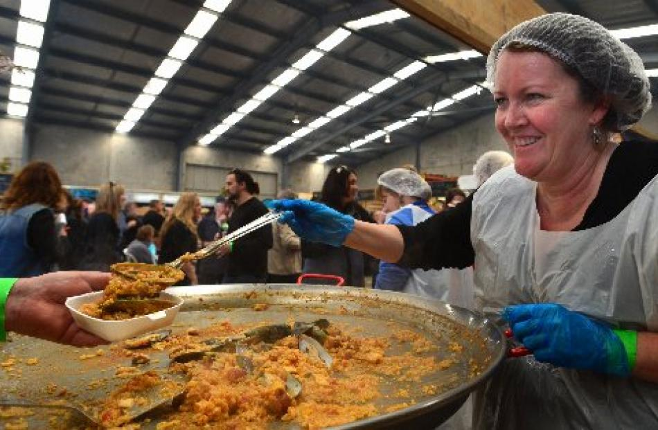 Kathy Scott, of Dunedin, serves paella to festival-goers.