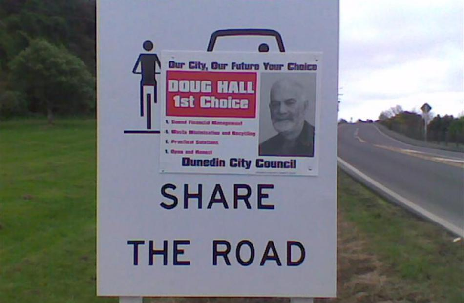 A stolen Doug Hall campaign poster shares space on a 'share the road' sign beside State Highway...