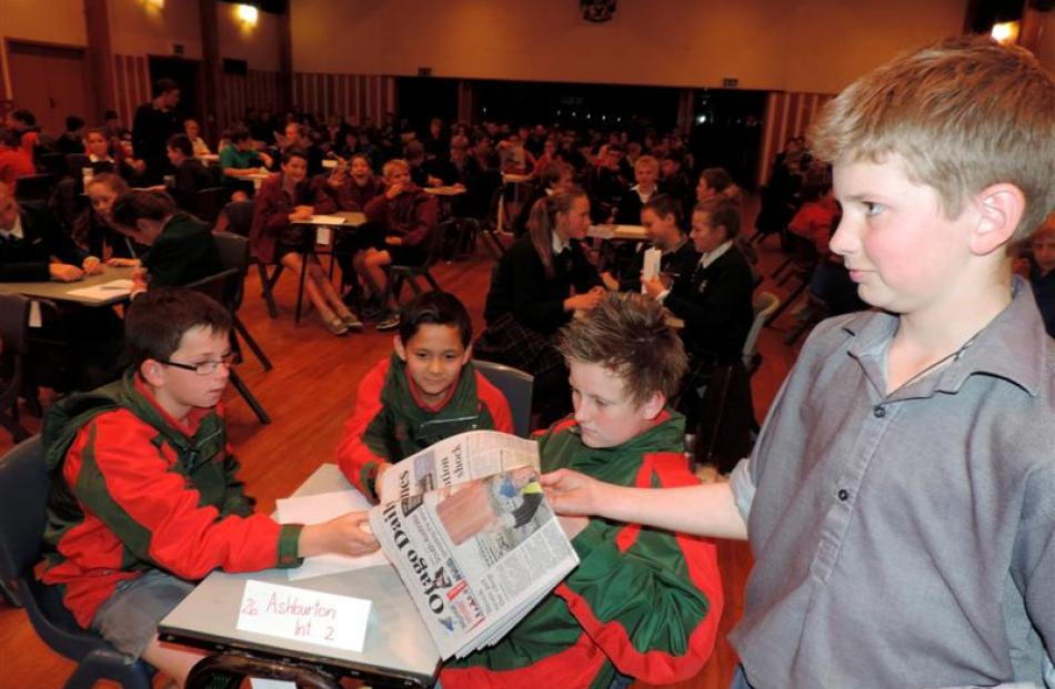Timaru Boys' High School's Charlie Stock (13) hands a newspaper to the Ashburton Intermediate 2...