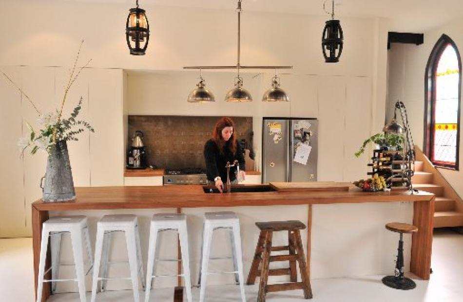 Jaimee Whiston in the kitchen. The stairs at right lead to the new mezzanine floor. Photo by...