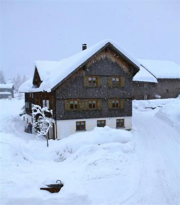 A Mellau farmhouse wears a blanket of snow.