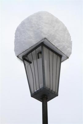 Snow on a street lamp.