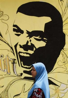 A Muslim woman walks past presidential candidate Mohamed Nasheed's  election campaign poster in...
