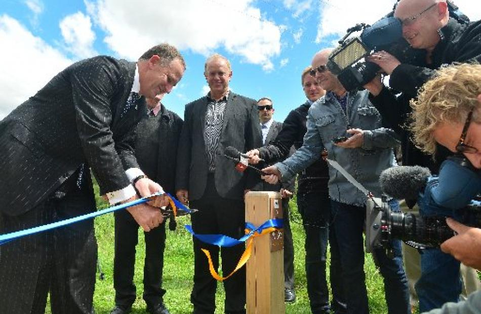 Prime Minister John Key cuts a ribbon at the Roxburgh end of the Clutha Gold Trail, for  the...