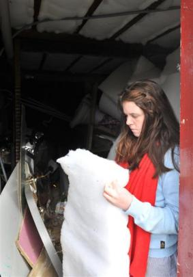 Letisha Nicholas (23), inspects the insulation used to line the basement. The material makes use...