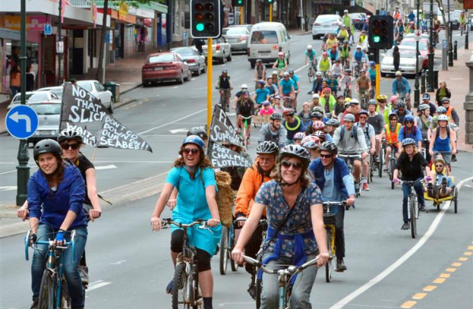 Drilling protesters cycle through the Exchange area in Dunedin yesterday.