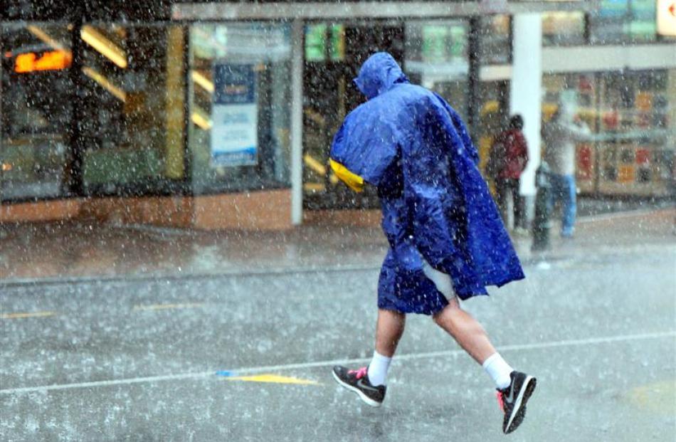 A pedestrian runs across George St in the rain.