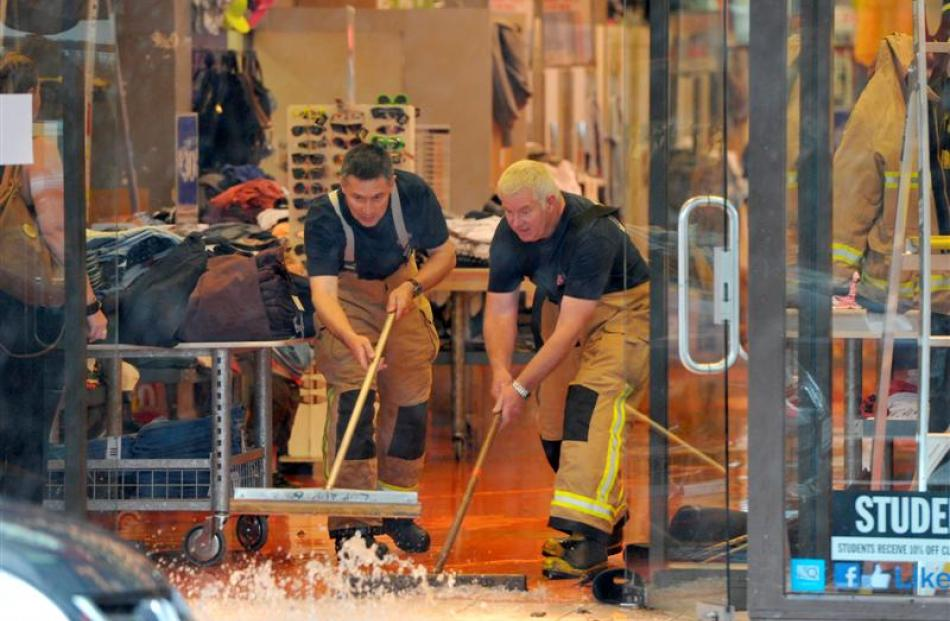 Lookout Point Senior Fire Officers Michael Loo (left) and Gerald Vorgers push water out of Jay...