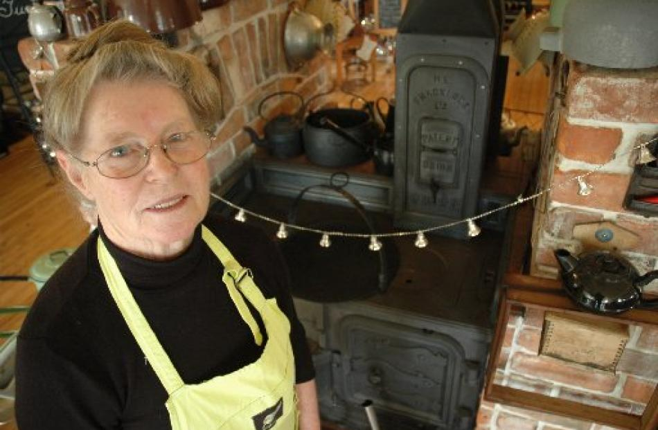 Helen McKay, of Yesteryears Museum Café, stands in front of the 1870 coal range on which she...