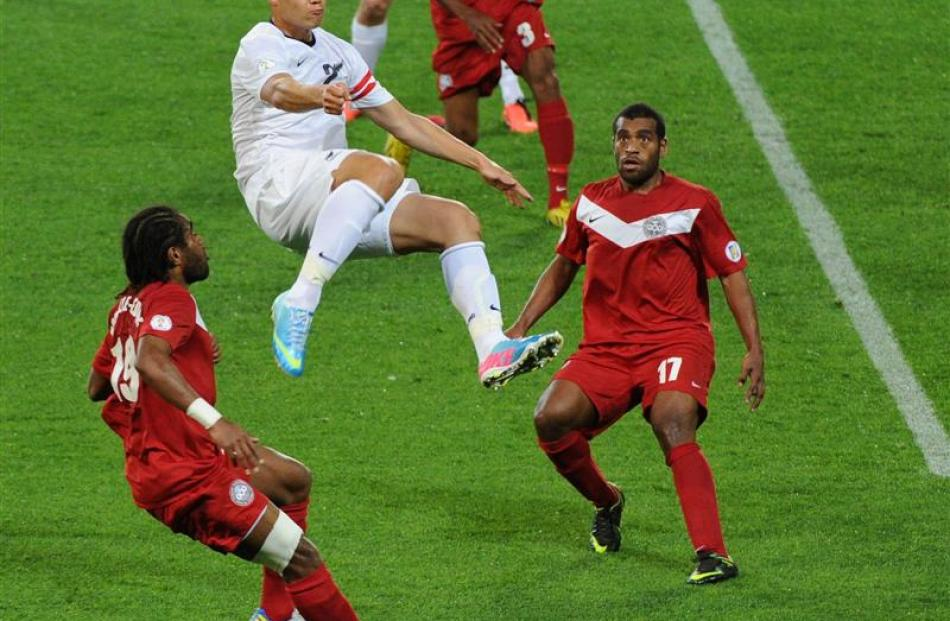 All Whites captain Winston Reid climbs above New Caledonia's defenders during the Fifa World Cup...