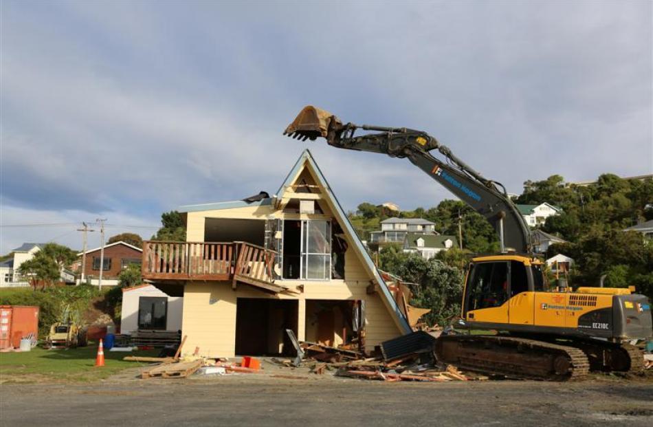 A Fulton Hogan tracked excavator knocks down the old Brighton Surf Life Saving Club building...