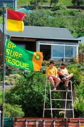 Surf lifesavers Sam Arnold (left) and Seth McPhee keep watch from a temporary platform at the...