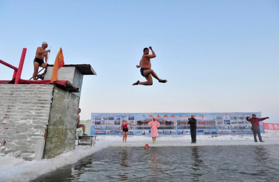 A swimmer jumps into the icy water of partially frozen Songhua River. REUTERS/Sheng Li