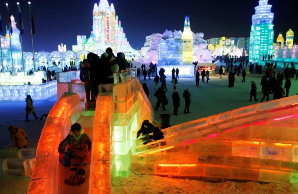 A visitor rides a slide on an ice sculpture during a light-up rehearsal. REUTERS/Kim Kyung-Hoon