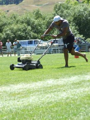 Taika Brooks, of Queenstown, winner of the push mower race, powers through the course on Saturday.