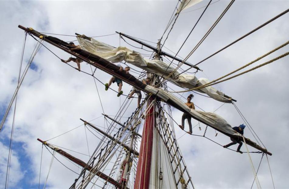 The crew aloft furl the fore square sails.