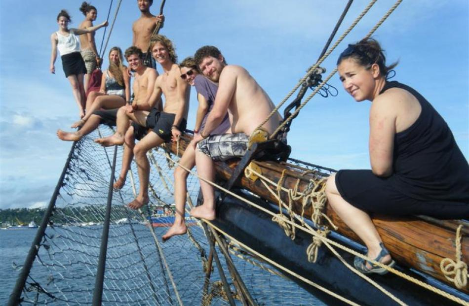 The crew hanging on the jib boom of the Alvei, happy to be arriving in Suva, Fiji.