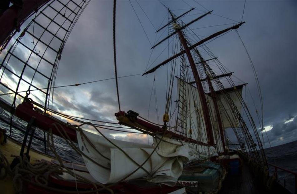 The main sails furled, the fore square and gaff sails set in the background.