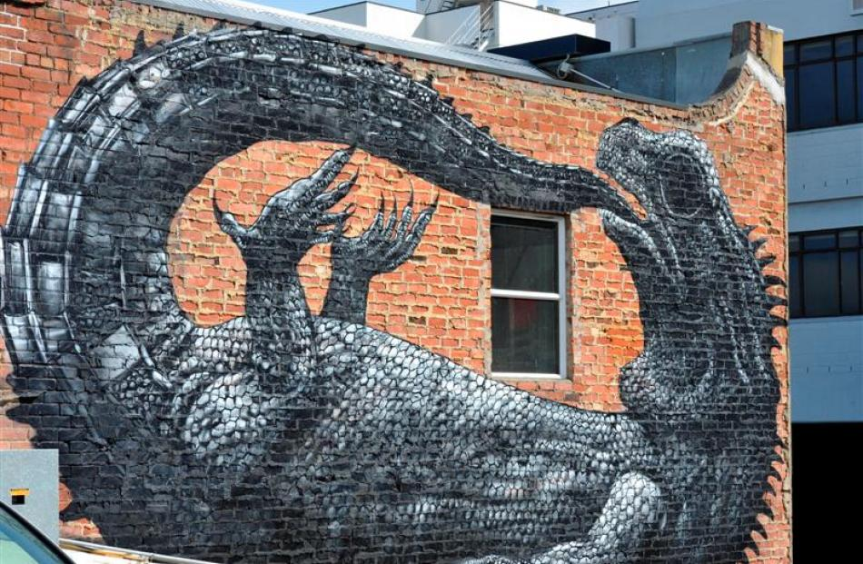 The finishing touches are applied to a two-storey spray-painted mural of a tuatara in Bath St,...