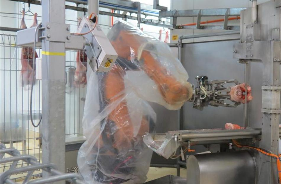 A robotic arm puts a meat cut through a bandsaw at the Finegand freezing works near Balclutha.