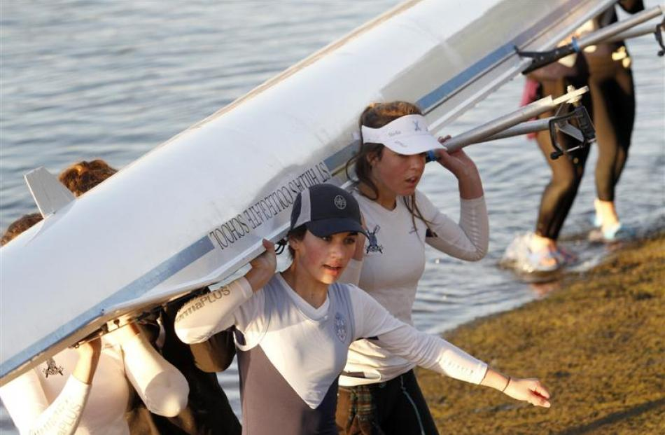 St Hilda's rowers Lili Sabonadiere (left) and Stella Keown help carry their boat back to the...