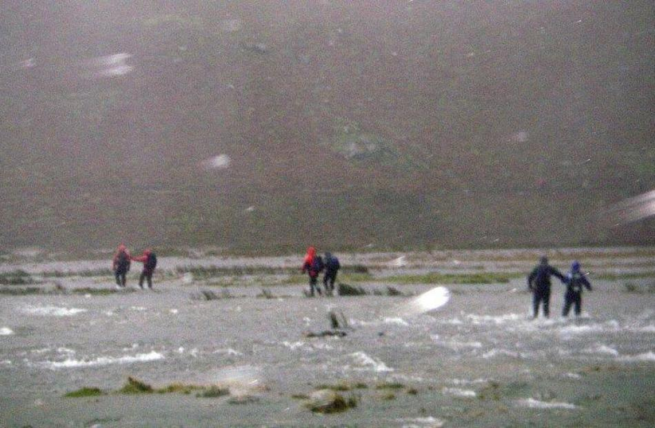 Competitors cross a stream.