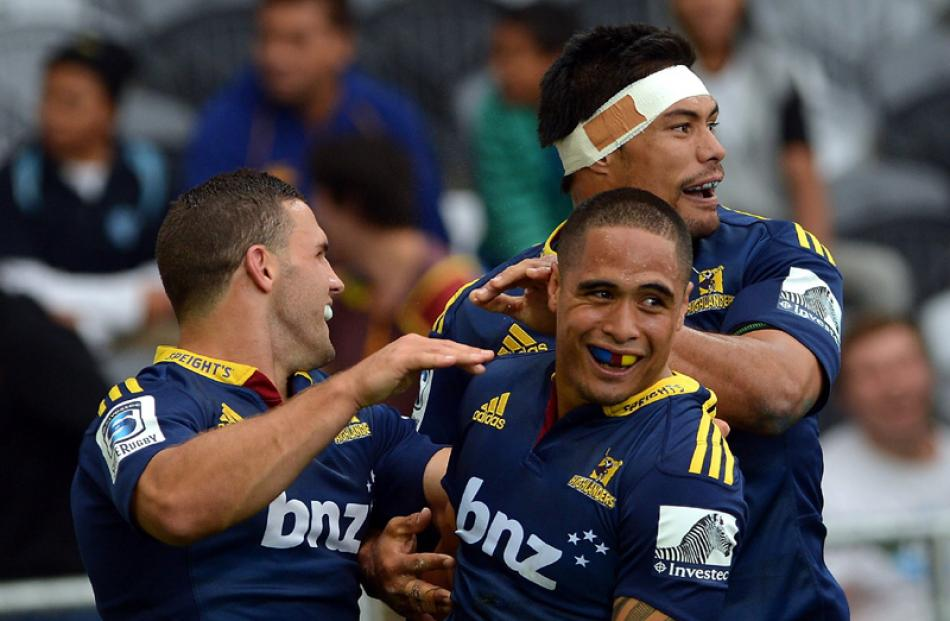 Highlanders (from left) Shaun Treeby, Aaron Smith and Shane Christie celebrate Smith's try.