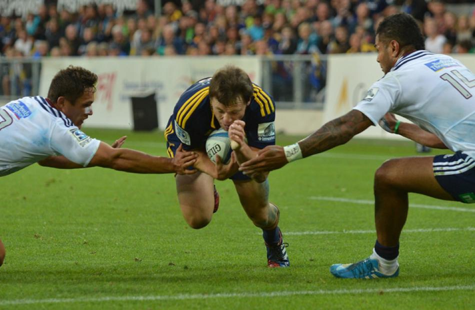 Highlander Ben Smith goes over to score a try with Blues players from left number 13 Jackson...