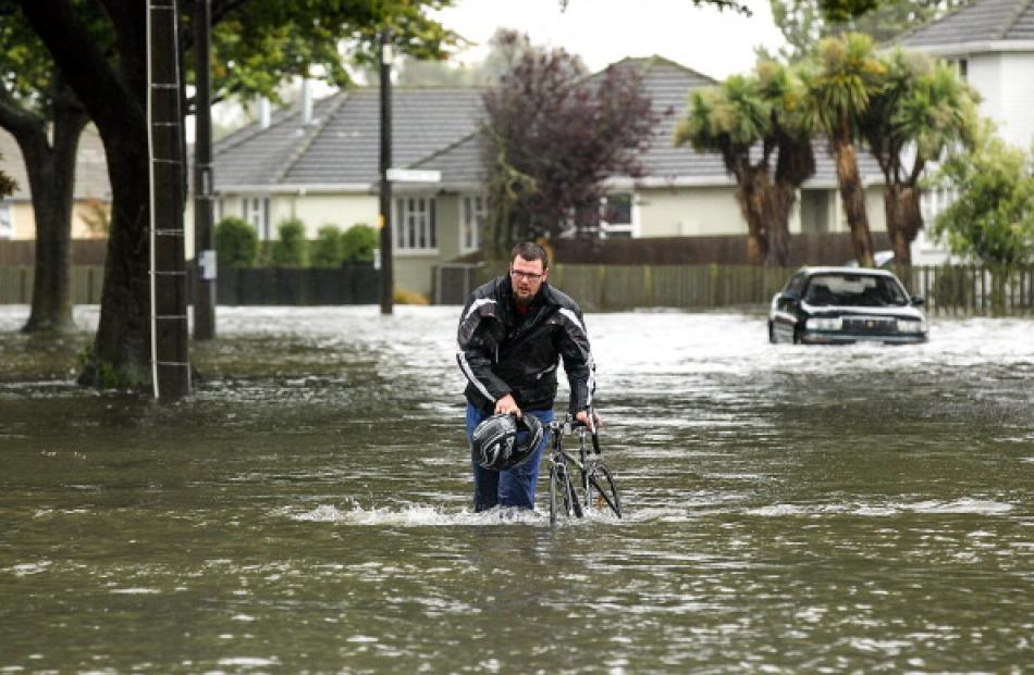 A cyclist wades through flooded streets in Edgeware, Christchurch. Photo by Getty
