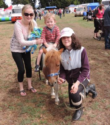 Brayden Pierce (3) hitches a ride on Bubbles at the Winchester Show, led by Sarah Purcell (right)...