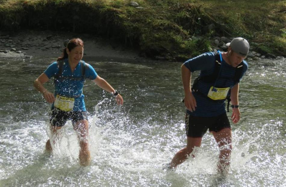 Korina Somerville, of Winton, and Nigel Robertson, of Invercargill, cross the Arrow River.