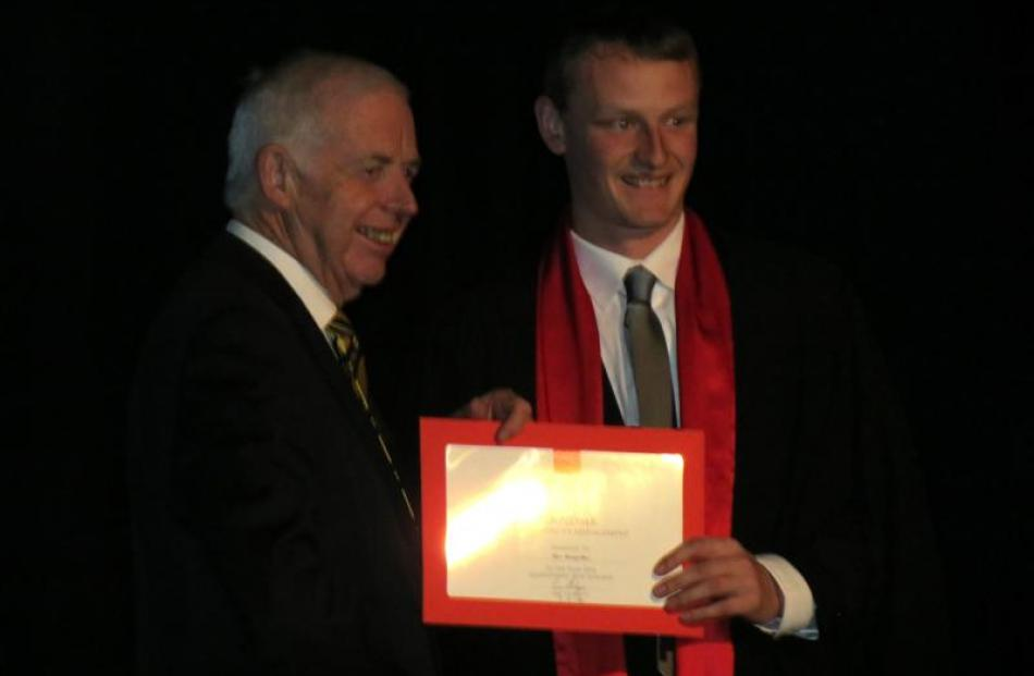 Graduate Alex Hampshire is awarded his certificate by college chairman Sir Eion Edgar during...