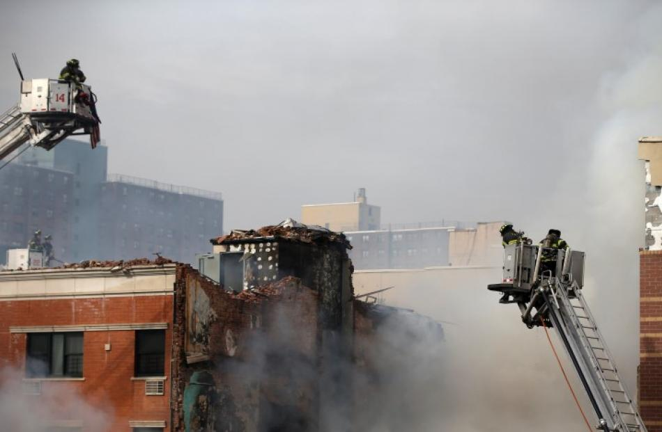 Firefighters try to extinguish a fire caused by the blast. REUTERS/Shannon Stapleton