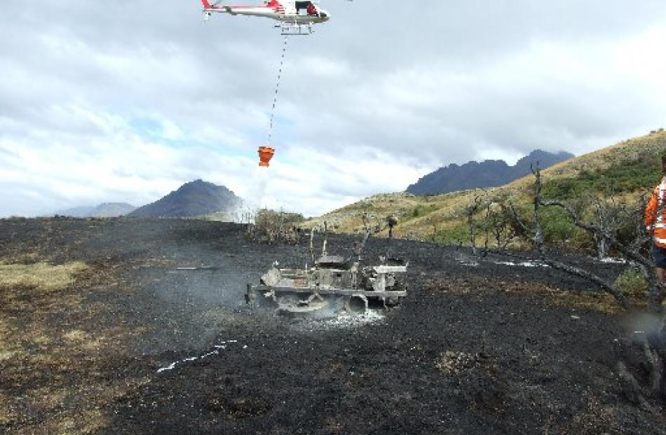 A helicopter drops water as the charred remains of the lawnmower, believed to have caused the...