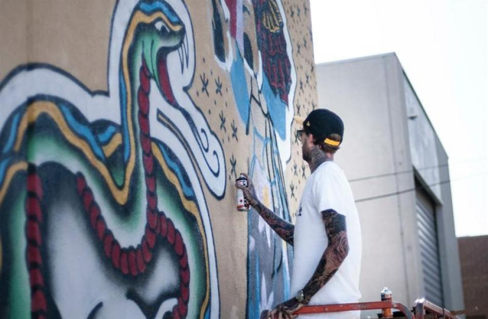 Street artist Steen Jones, of Melbourne, works on an Authority Clothing mural on Beith St, in...