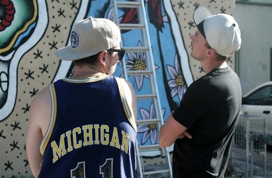 Sydney-based street artist Alex Lehours (left) and  Christopher Skyner  inspect a mural painted...
