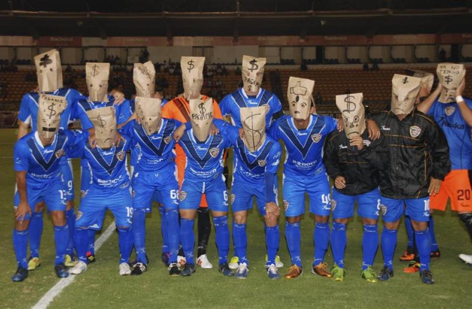 Players of the Mexican second division football team Celaya team pose with brown paper bags over...