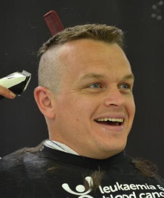 Constable Matt Davidson, of Dunedin police, has his hair shaved at Farmers  in Dunedin on...