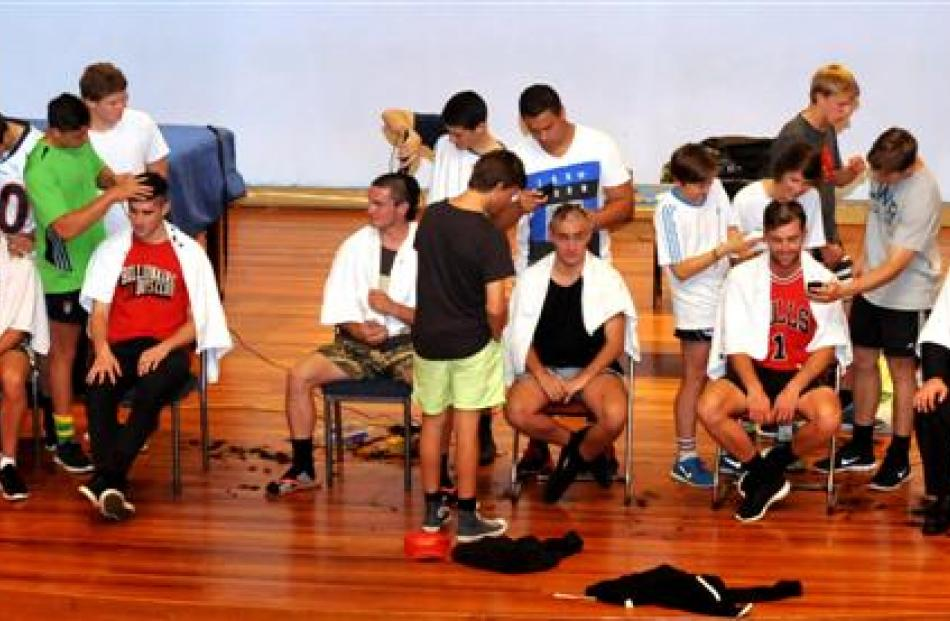 Otago Boys' High School pupils and staff line up to have their heads shaved to raise funds for...