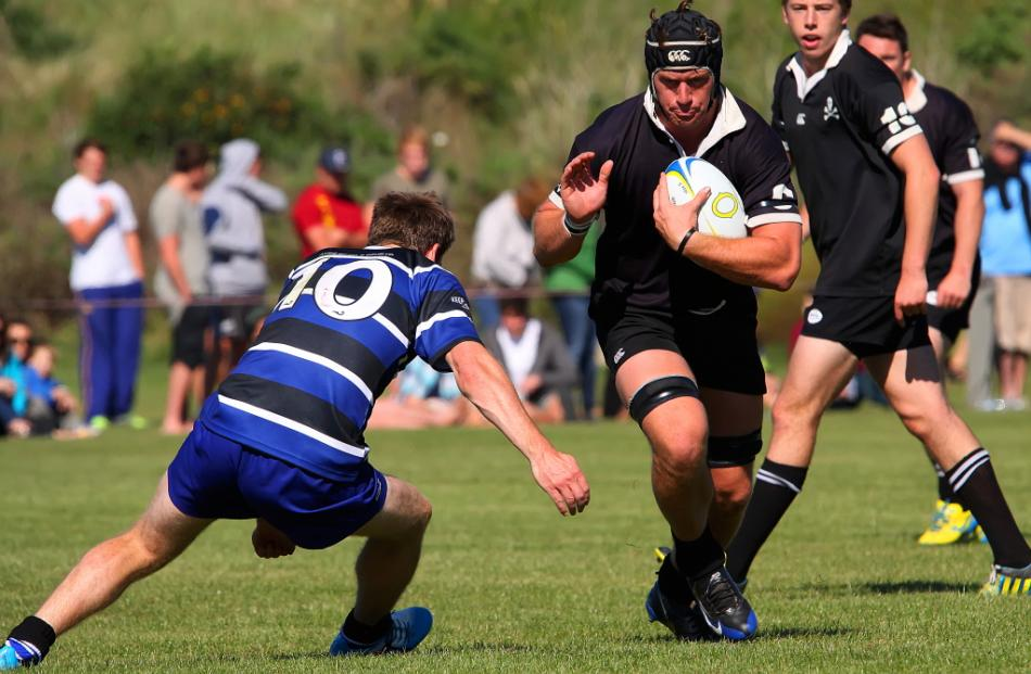 Pirates blindside flanker Ben Sexton prepares to be tackled by Kaikorai No 10, Cameron Rutherford...