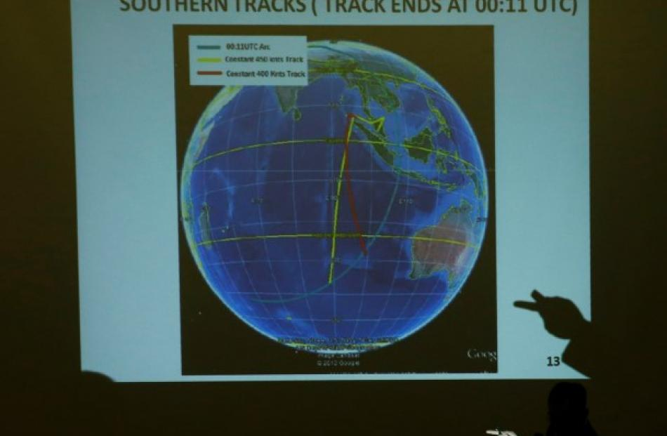 Malaysian Lieutenant General Ackbal Samad shows a possible track of MH370 to relatives of...